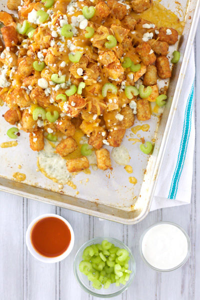 Buffalo Chicken Tater Tot Nachos | BourbonAndHoney.com -- These delicious Tater Tot Nachos are cheesy, bacon-y and delicious! They're the perfect appetizer for a party!