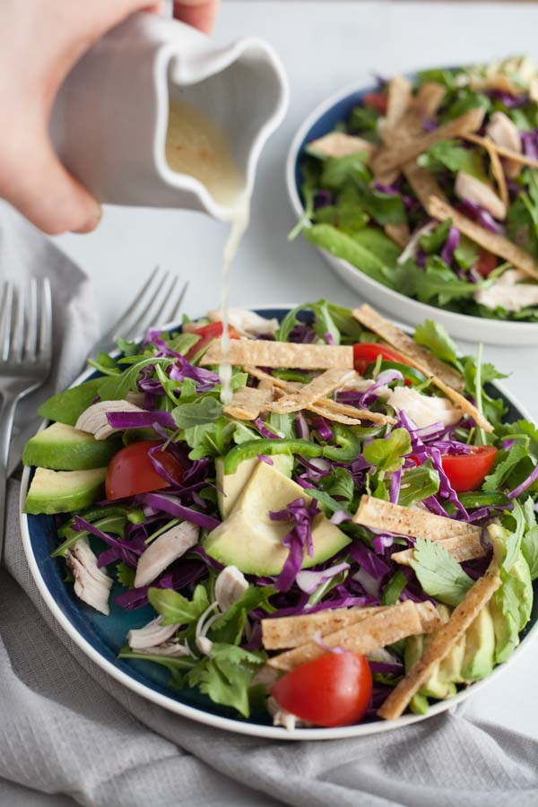 Avocado and Chicken Tortilla Salad | BourbonandHoney.com -- This Avocado and Chicken Tortilla Salad is piled with avocado, spicy jalapeño, crunchy tortilla strips and a bright lime dressing for a hearty weeknight salad.