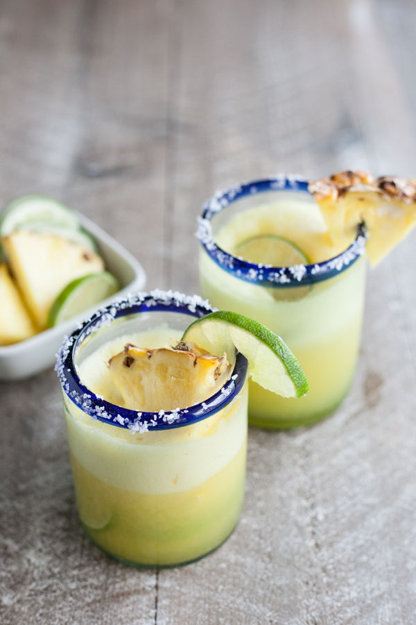 Frozen Pineapple Margaritas | BourbonandHoney.com -- Sweet, frosty and totally refreshing, these tequila spiked frozen pineapple margaritas are going to sweeten your weekend!