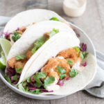 Coconut Shrimp Tacos with Cilantro Cabbage Slaw | BourbonandHoney.com -- Crispy, crunchy and totally delicious, these Coconut Shrimp Tacos are stuffed with cilantro cabbage slaw and a drizzle of spicy aioli.