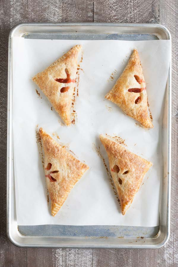 Easy Strawberry Rhubarb Turnovers | BourbonandHoney.com -- Sweet, tart and perfectly flaky these Strawberry Rhubarb Turnovers are a deliciously easy spring treat or brunch recipe!