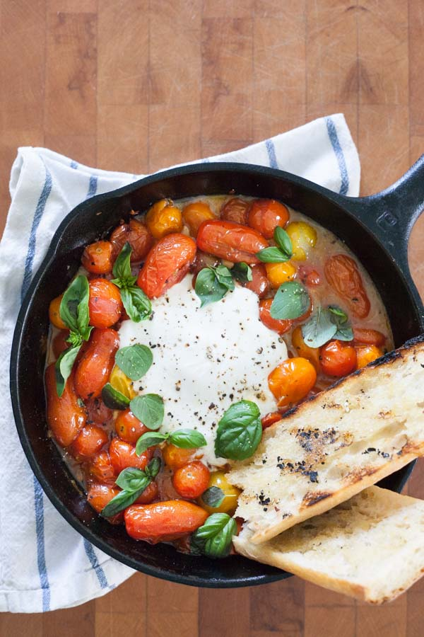 Grilled Tomatoes with Burrata and Basil | BourbonandHoney.com -- This summery skillet recipe of Grilled Tomatoes with Burrata and Basil is a great appetizer, light lunch or dinner served over pasta!