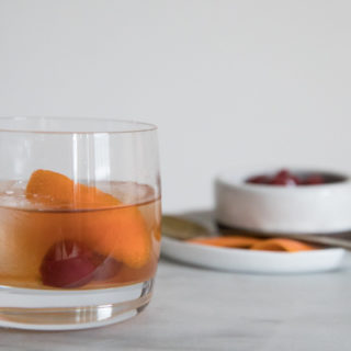 Low ball cocktail glass on marble counter. Large ice cubes in the glass with cherries and orange peel garnishing a Bourbon and Honey Old Fashioned Cocktail. Additional Garnishes in the background.